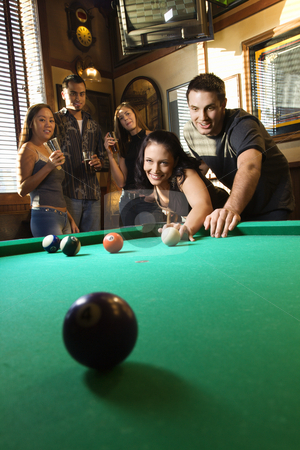 Group playing billiards. stock photo, Young caucasian woman receiving advice on shooting pool ball while playing billiards. by Iofoto Images
