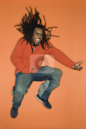 Man jumping with enthusiasm. stock photo, African-American mid-adult man on orange background jumping while playing air guitar. by Iofoto Images