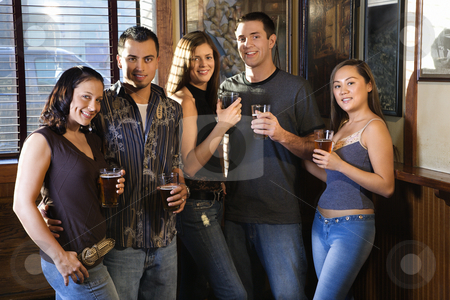 Group at nightclub. stock photo, Group of young friends hanging out in pub and drinking beer. by Iofoto Images