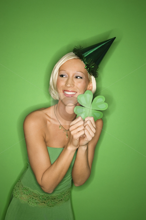 Woman holding shamrock. stock photo, Portrait of smiling young adult Caucasian blond woman on green background wearing party hat and holding shamrock for Saint Patricks Day celebration. by Iofoto Images