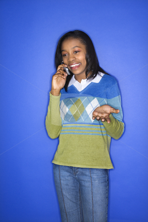 Girl talking on cellphone. stock photo, Portrait of African-American teen girl smiling and talking on cellphone standing in front of blue background. by Iofoto Images