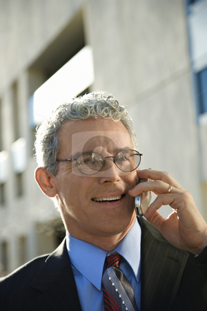 Man on cellphone. stock photo, Prime adult Caucasian man in suit smiling and talking on cellphone in urban setting. by Iofoto Images