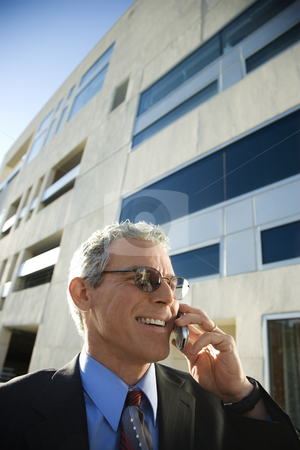 Man talking on cellphone. stock photo, Prime adult Caucasian man in suit smiling and talking on cellphone in urban setting. by Iofoto Images