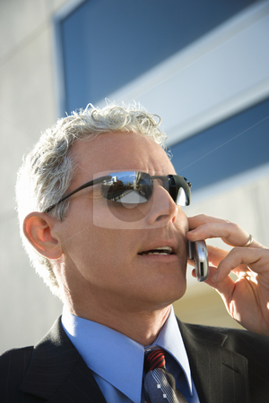 Businessman talking on cellphone. stock photo, Close up side view of prime adult Caucasian man in suit talking on cellphone in urban setting. by Iofoto Images