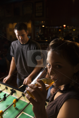 Woman drinking beer. stock photo, Young woman drinking beer and looking at viewer while man plays foosball in pub. by Iofoto Images