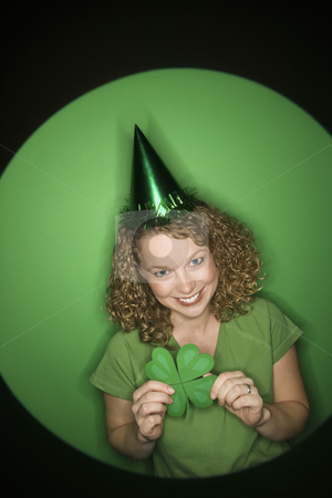 Woman holding shamrock. stock photo, Vignette of smiling young adult Caucasian woman on green background wearing Saint Patricks Day hat and holding shamrock. by Iofoto Images