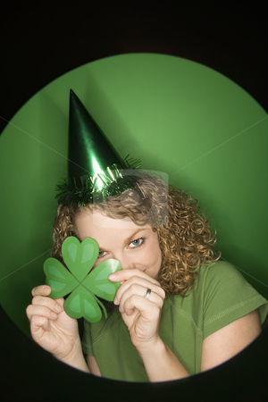 Woman celebrating St. Patty. stock photo, Vignette of young adult Caucasian woman on green background wearing Saint Patricks Day hat and holding shamrock. by Iofoto Images