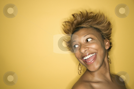Expressive smiling woman. stock photo, Portrait of smiling African-American young adult woman on yellow background. by Iofoto Images