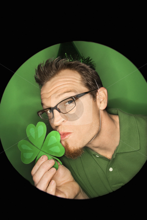 Man kissing shamrock. stock photo, Vignette of adult Caucasian man on green background wearing Saint Patricks Day hat and kissing shamrock. by Iofoto Images