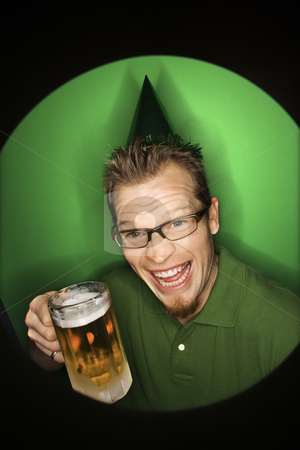 Man holding beer. stock photo, Vignette of adult Caucasian man on green background wearing green hat and holding beer. by Iofoto Images