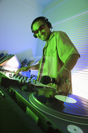 Male DJ with hand on record. stock photo, Asian young adult male DJ wearing sunglasses behind mixing equipment with hand on record turntable looking at viewer smiling. by Iofoto Images