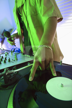 Man spinning record. stock photo, Close-up of Asian young adult male DJ's hand spinning vinyl record. by Iofoto Images