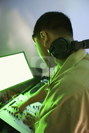 Man with audio equipment. stock photo, Rear view of Asian young adult male DJ mixing music on equipment. by Iofoto Images