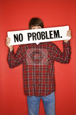 Boy holding sign. stock photo, Portrait of Caucasian teen boy holding no problem sign under his eyes. by Iofoto Images