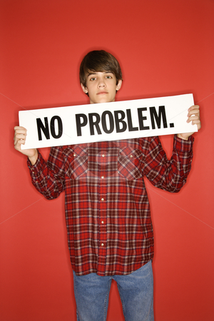 Boy holding sign. stock photo, Portrait of Caucasian teen boy holding no problem sign under his chin. by Iofoto Images