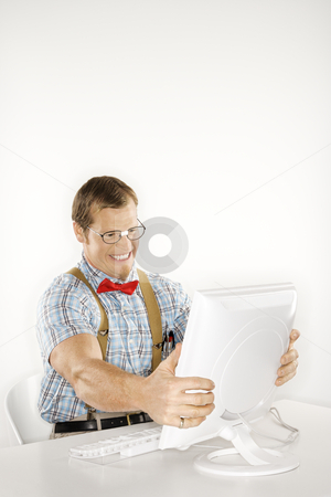 Nerd with computer. stock photo, Caucasian young man dressed like nerd holding computer monitor in frustration. by Iofoto Images