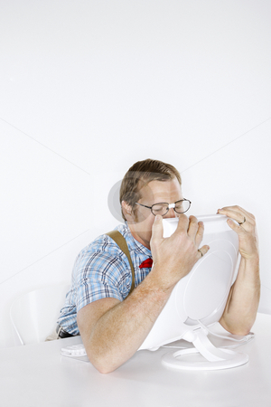 Man hugging computer. stock photo, Caucasian young man dressed like nerd embracing computer with face pressed to monitor. by Iofoto Images