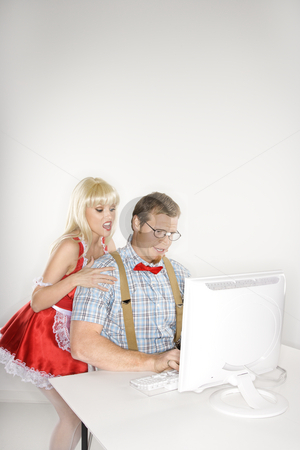 Couple with computer. stock photo, Caucasian young man dressed like nerd with Caucasian young blonde woman dressed in french maid outfit looking over shoulder. by Iofoto Images