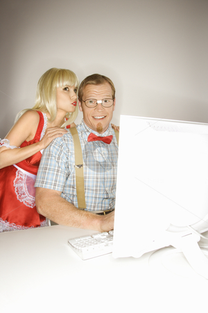 Woman flirting with nerd. stock photo, Caucasian young blonde woman dressed in french maid outfit whispering to Caucasian young man sitting behind computer dressed like nerd. by Iofoto Images