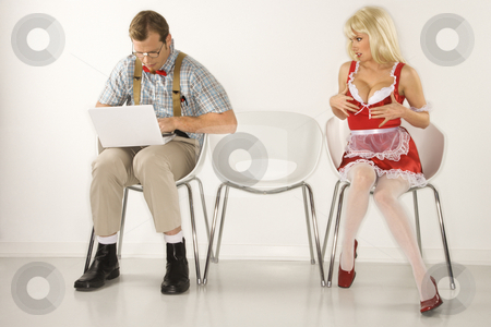 Woman flirting with man. stock photo, Caucasian young man dressed like nerd sitting with laptop with Caucasian young blonde woman trying to distract him with cleavage. by Iofoto Images
