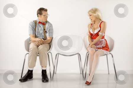 Attraction of man and woman. stock photo, Caucasian young man dressed like nerd and Caucasian young blonde woman in french maid outfit sitting and looking at eachother. by Iofoto Images