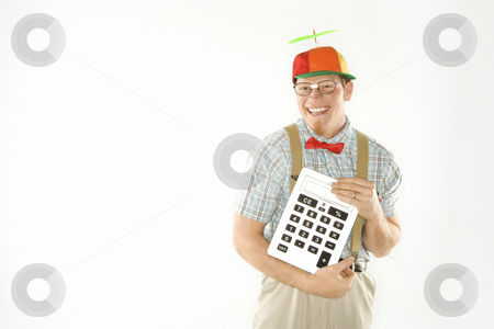 Nerd holding calculator. stock photo, Caucasian young man dressed like nerd wearing beanie and smiling while holding large calculator. by Iofoto Images
