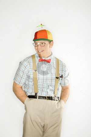 Man dressed like nerd. stock photo, Caucasian young man dressed like nerd wearing propeller cap with hands in pockets. by Iofoto Images