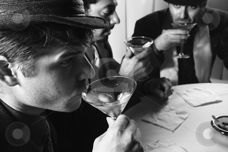 Retro men drinking. stock photo, Three Caucasian prime adult males in retro suits sitting at table drinking cocktails. by Iofoto Images