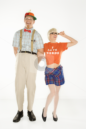 Nerd and beautiful woman. stock photo, Caucasian young man dressed like nerd wearing propeller hat with blonde Caucasian young woman in nerdy eyeglasses and tshirt reading I love nerds and plaid skirt. by Iofoto Images