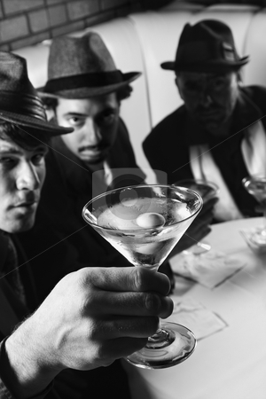 Retro men drinking martinis. stock photo, Three Caucasian prime adult males in retro suits sitting at table with martini. by Iofoto Images