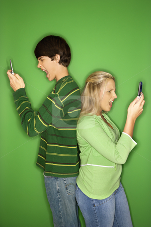 Boy and girl on cellphones. stock photo, Portrait of Caucasian teen boy and girl on cellphones standing with backs to eachother against green background. by Iofoto Images