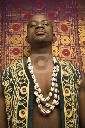 Man in African garments. stock photo, Low angle portrait of African-American mid-adult man wearing embroidered African vest and beads. by Iofoto Images