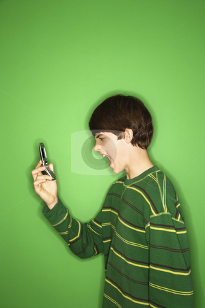 Boy yelling into phone. stock photo, Portrait of Caucasian teen boy screaming at cellphone. by Iofoto Images