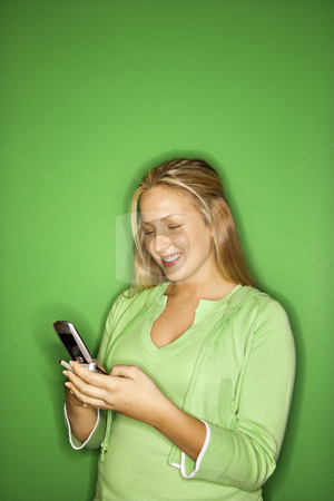 Girl using cellphone. stock photo, Portrait of blond Caucasian teen girl smiling at cellphone against green background. by Iofoto Images