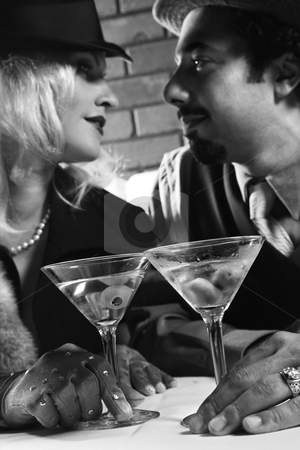 Retro couple at bar. stock photo, Caucasian prime adult retro male and female looking into eachother's eyes. by Iofoto Images
