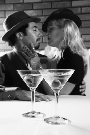 Retro couple with martinis. stock photo, Caucasian prime adult retro male and female looking into eachother's eyes. by Iofoto Images