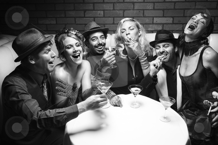 Retro group at nightclub. stock photo, Group of Caucasian prime adult retro males and females sitting at table in lounge laughing. by Iofoto Images