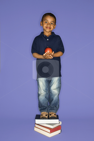 Boy standing on books. stock photo, African American male child standing on stack of books. by Iofoto Images
