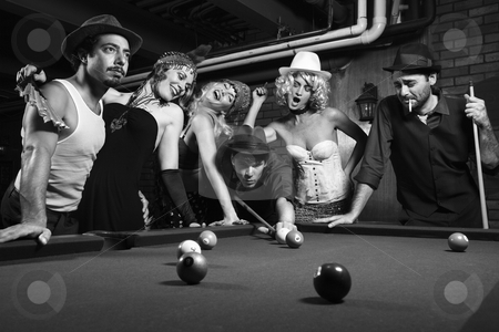 Retro group playing pool. stock photo, Group of Caucasian prime adult retro males and females trying to distract man as he takes pool shot. by Iofoto Images
