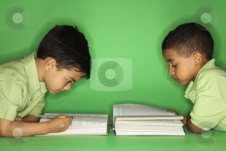 Boys lying and reading. stock photo, Hispanic and African American male child lying reading. by Iofoto Images