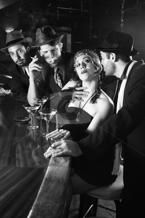 Center of attention. stock photo, Caucasian prime adult retro female sitting at bar surrounded by suitors. by Iofoto Images