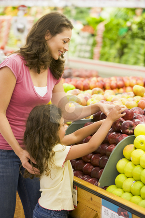 Mother and daughter in produce section stock photo, Mother and daughter in produce section of supermarket by Monkey Business Images