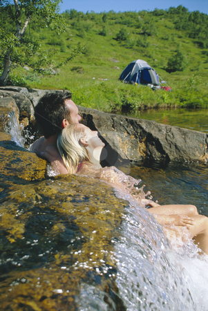 Couple sitting in running water on lakes edge stock photo,  by Monkey Business Images