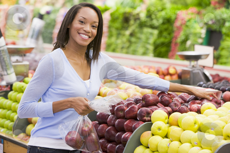 Woman shopping in produce department stock photo, Woman shopping in produce department of supermarket by Monkey Business Images