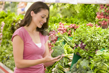 Woman shopping in produce section stock photo, Woman shopping in produce section of supermarket by Monkey Business Images