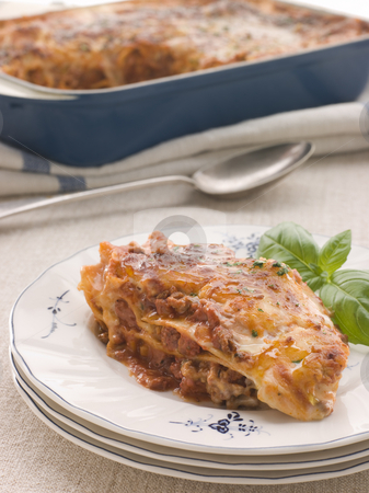 Portion of Lasagne with Basil stock photo, Plate with a Portion of Lasagne decorated with Basil by Monkey Business Images