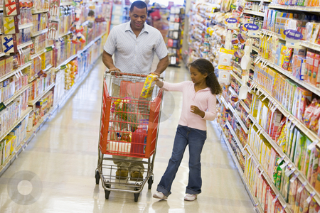 Father and daughter shopping in supermarket stock photo, Father and daughter grocery shopping in supermarket by Monkey Business Images