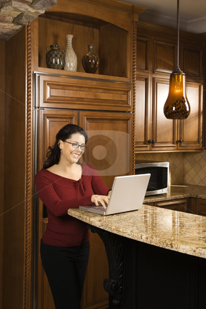 Woman on laptop. stock photo, Caucasian woman standing at kitchen counter typing on laptop computer and smiling. by Iofoto Images