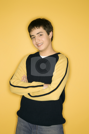 Teen boy portrait. stock photo, Portrait of smiling Caucasian teen boy with crossed arms standing against yellow background. by Iofoto Images