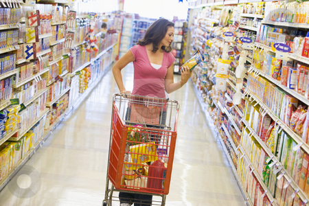 Woman shopping in supermarket aisle stock photo, Woman pushing trolley along supermarket grocery aisle by Monkey Business Images